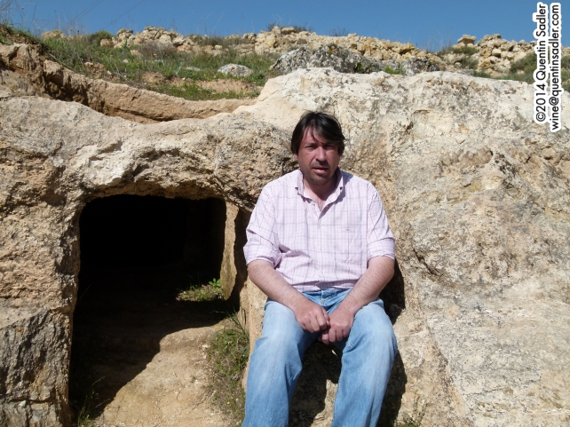 Fabrice sitting on the mourner's seat carved into the rock of the ancient tomb.